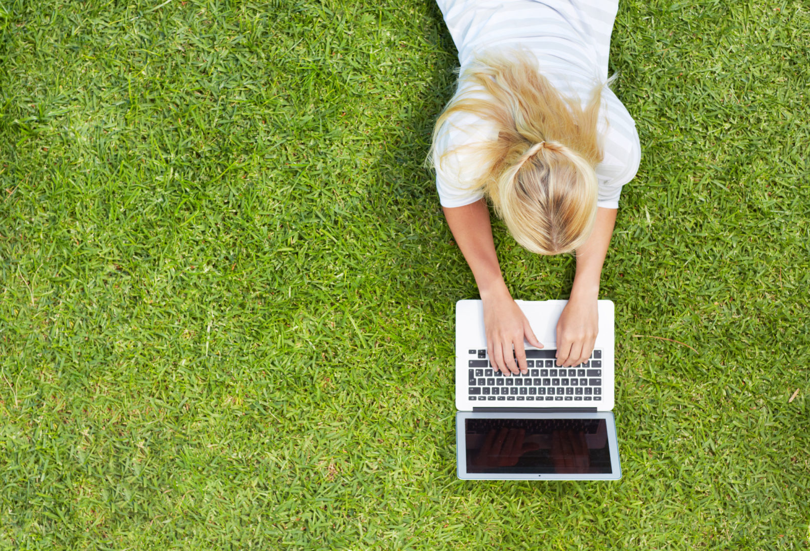 High angle shot of a young woman using a laptop while lying on the grass